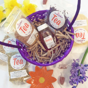 Loose leaf teas, sweeteners, and honey and tucked into a purple basket and surrounded by flowers.