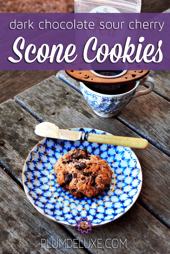 A dark chocolate sour cherry scone cookie sits on a blue and white plate with a knife and pat of butter.