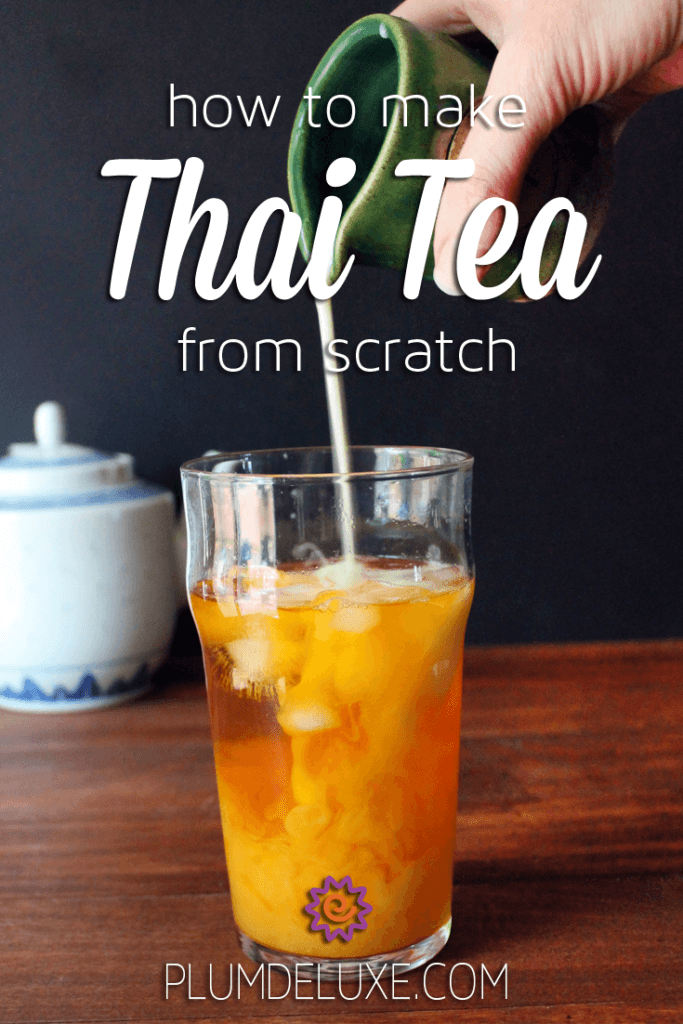Cream is poured from an earthenware pitcher into a glass of thai tea with ice.