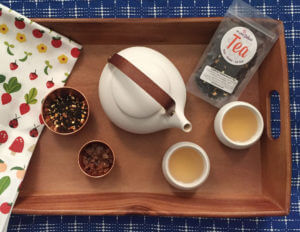 Overhead view of a wooden tea tray with a colorful tea towel, white tea pot, loose leaf tea, tea sugar, and teacups.