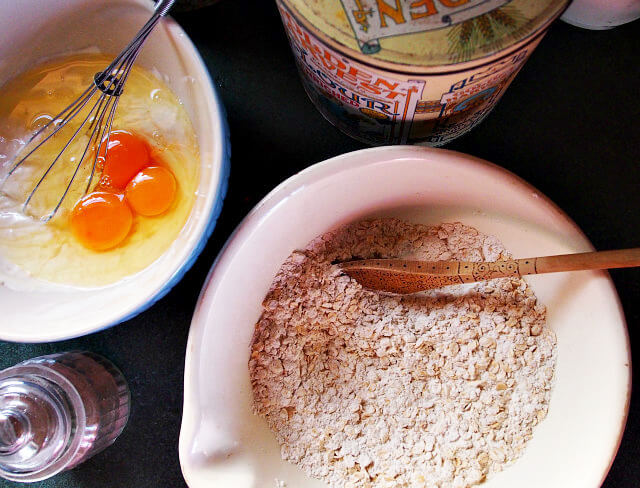 Overhead view of ingredients for grapefruit bread, including a bowl of flour and a bowl of cracked eggs.