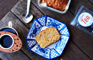 Overhead view of a slice of grapefruit bread resting on a blue and white plate, surrounded by a cup of tea, pewter heart scoop, loaf of bread, and bag of loose leaf tea.