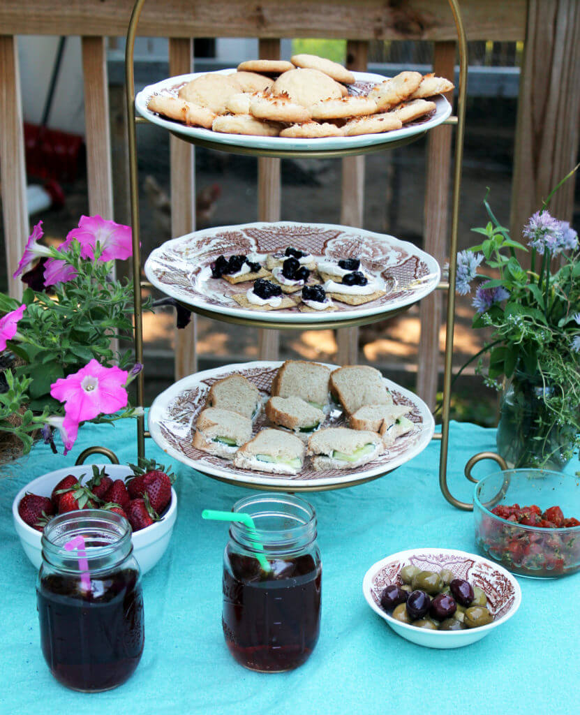 Tea sandwiches and cookies are arranged on a tiered server. Bowls of berries and olives and jars of iced tea surround it on a blue tablecloth.