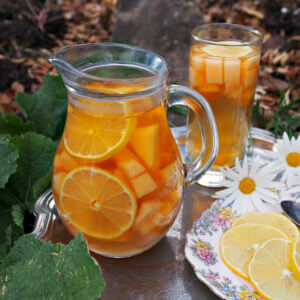 A pitcher full or fruit and iced tea sangria is in the foreground along with thinly sliced lemons on a floral plate. A glass of sangria and daisies are in the background.