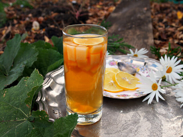 A tall glass is filled with fruit and iced tea sangria. Daisies and a plate with orange slices is in the background.
