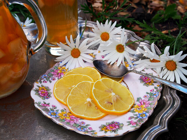 Thinly sliced lemons are arranged on a fancy floral plate with daisies.