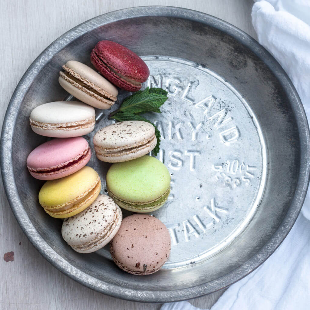 Overhead view of a tin dish half full of french macarons.