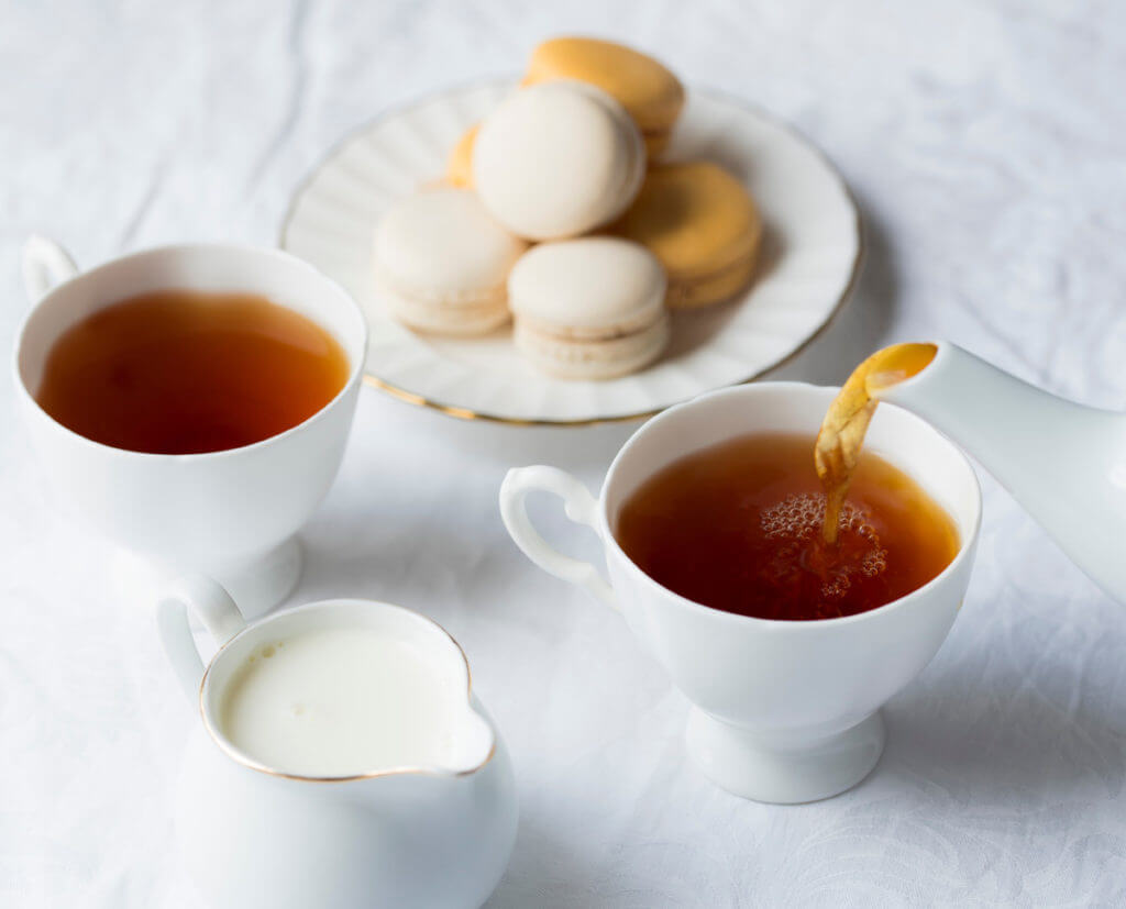 Tea is poured into white teacups. There is a white pitcher of cream in the foreground and a plate of french macarons in the background.