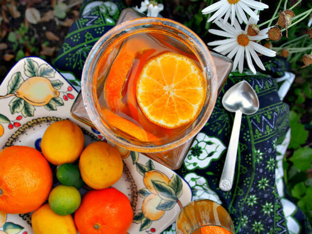 Overhead view of a large jar of citrus white sangria next to a platter of oranges, lemons, and limes.