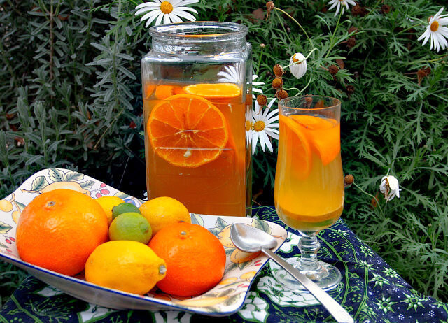 A large jar and glass of citrus white sangria sits on a table next to a platter of oranges, lemons, and limes with a background of daisies.