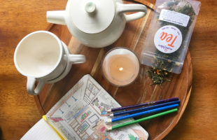 Overhead view of a teapot, teacups, candle, loose leaf tea, and a coloring book and colored pencils on a wooden tray.