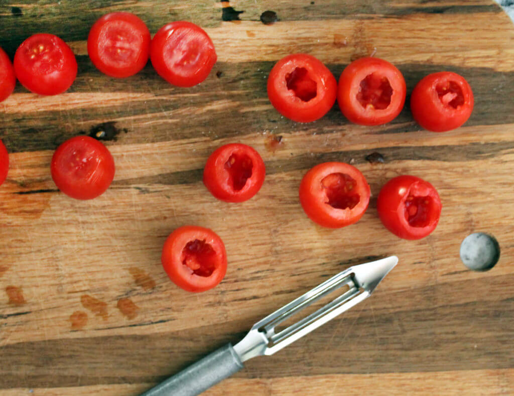 Cherry tomatoes are being hollowed out with a vegetable peeler on a wooden cutting board.