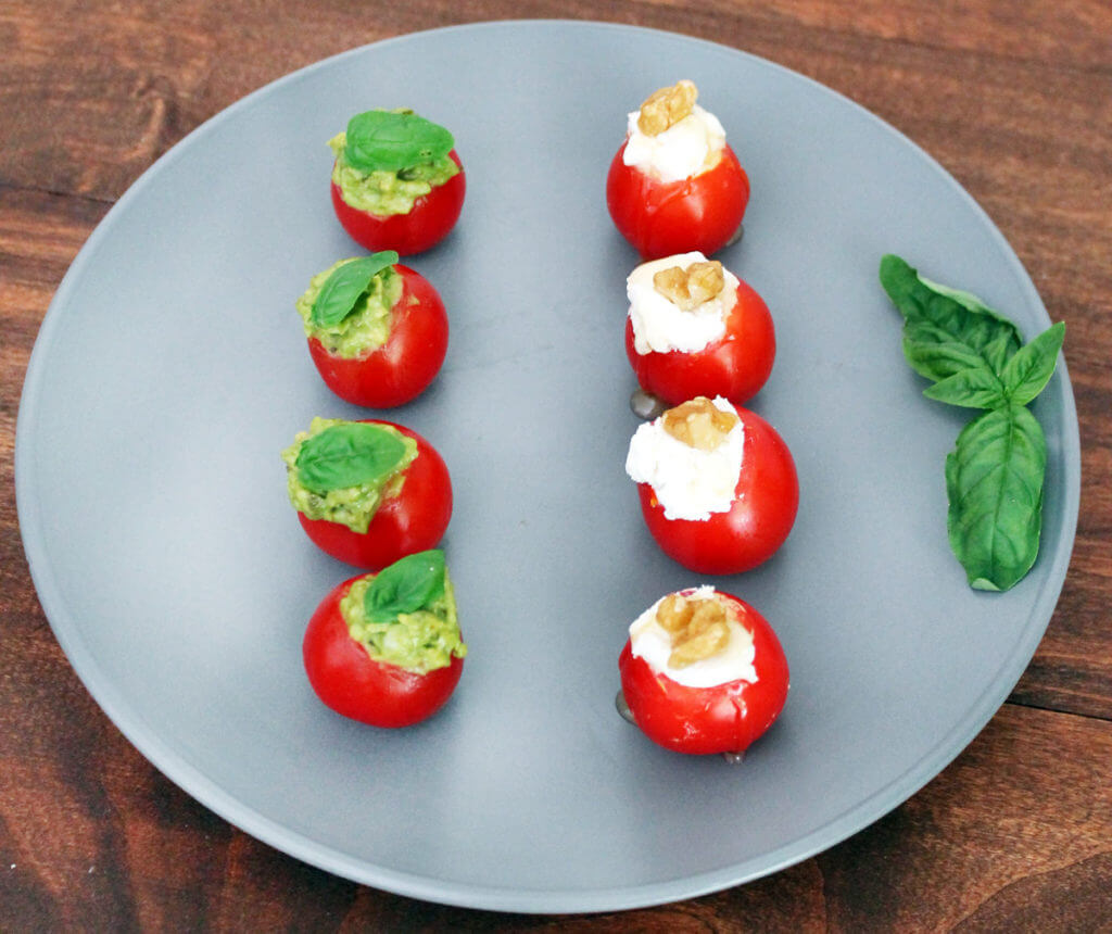 Two kinds of stuffed cherry tomatoes sit in rows on a plate.