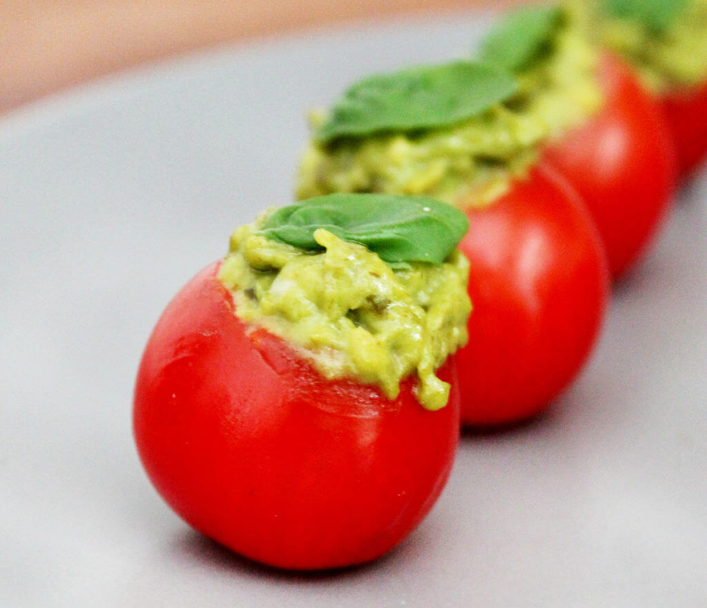 A row of avocado pesto stuffed cherry tomatoes sits on a plate.