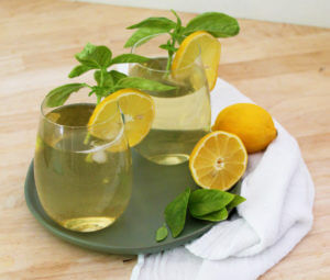 Two glasses of sparkling iced tea with green tea and lemonade are garnished with lemons and fresh basil.