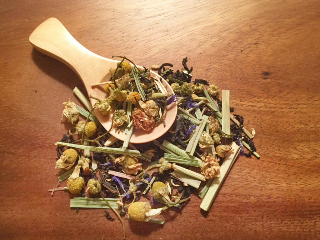 Closeup of a wooden scoop of loose leaf herbal tea on a wooden cutting board.