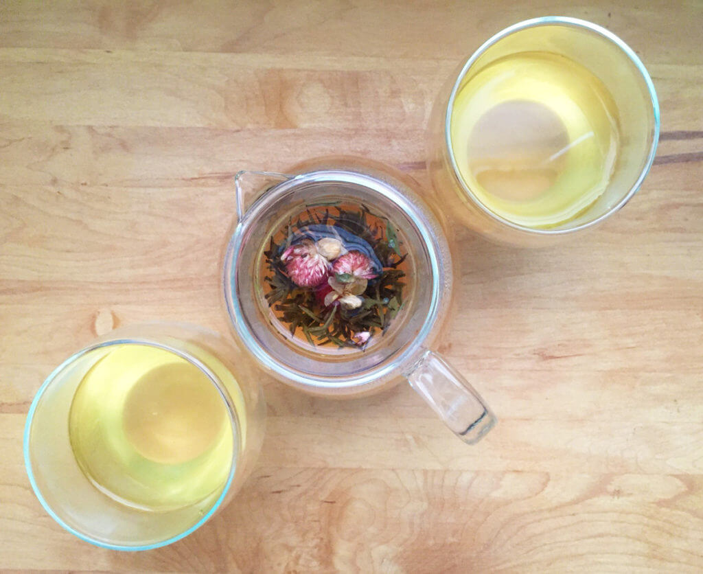 Overhead view of a glass pot of loose leaf tea with two glass teacups.