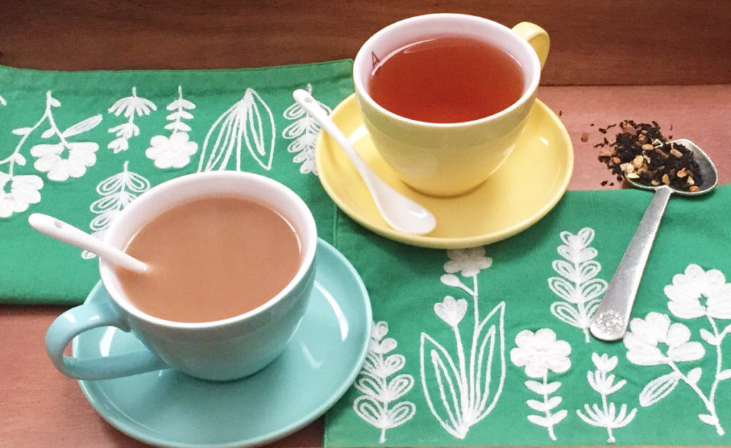 Blue and yellow teacups sit on a green and white floral tea towel on a wooden tray, with a scoop of loose leaf tea.