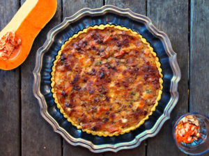 Overhead view of a butternut squash tart with a glass of squash seeds, and a halved butternut squash.