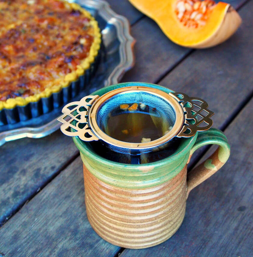 A cup of tea with a Victorian tea infuser. A butternut squash tart sits in the background.