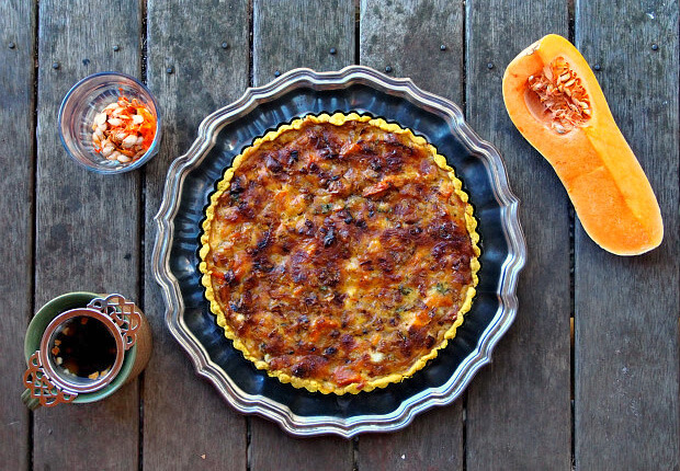 Overhead view of a butternut squash tart with a cup of tea, a glass of squash seeds, and a halved butternut squash.