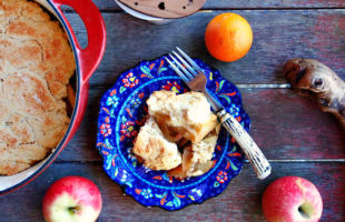 Overhead view of a blue plate of apple slump surrounded by apples, oranges, a cup of tea, and apple slump baked in a red crock.