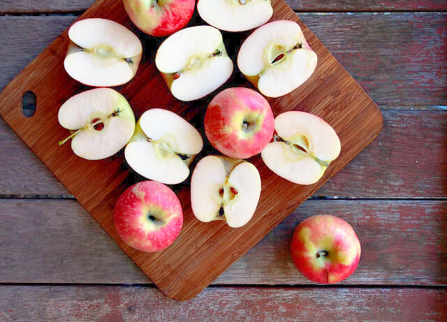 Overhead view of halved apples piled on a wooden cutting board.