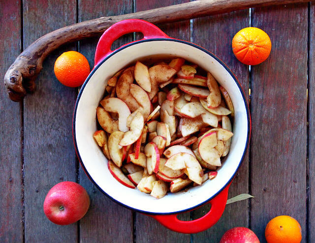 Overhead view of sliced apples tossed with spices in a red baking crock.