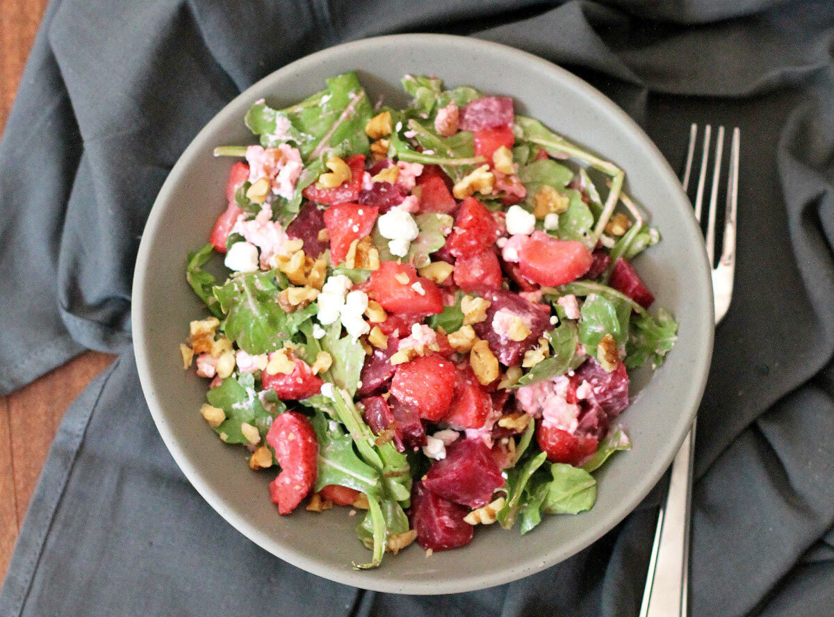 Overhead view of a roasted strawberry beet salad with balsamic dressing.