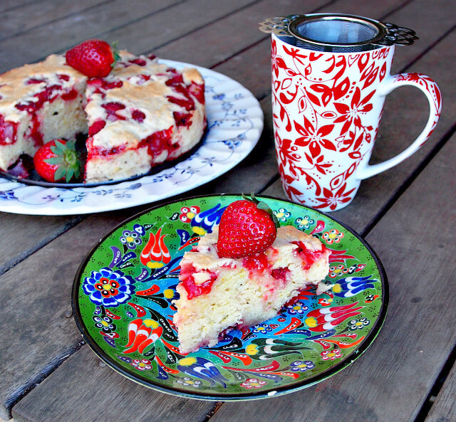A slice of strawberry buckle cake sits on a green floral plate. A red and white mug of tea sits in the background with the rest of the cake on a blue and white platter.