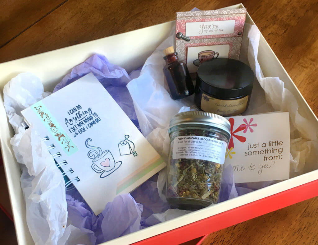 A tea self care package includes loose leaf tea, a journal, bath salts, and more.