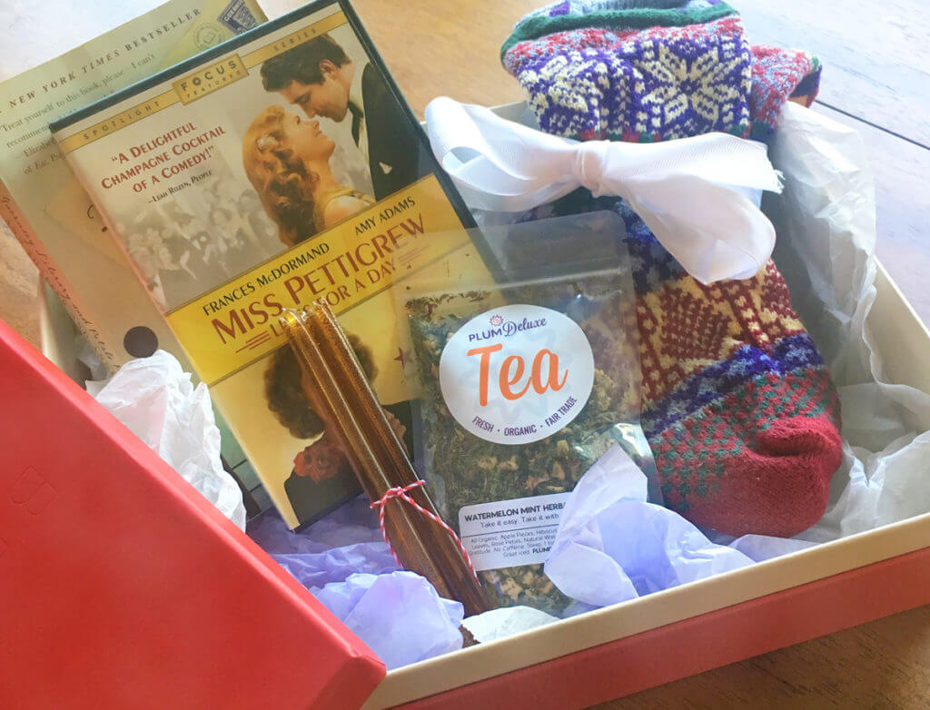 A sick day tea care package includes tea, honey sticks, fuzzy socks, a movie, and a book.