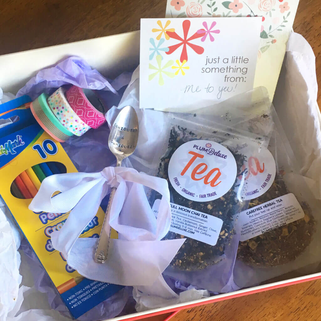 A tea party care package contains tea, a stamped teaspoon, a coloring book, and colored pencils.