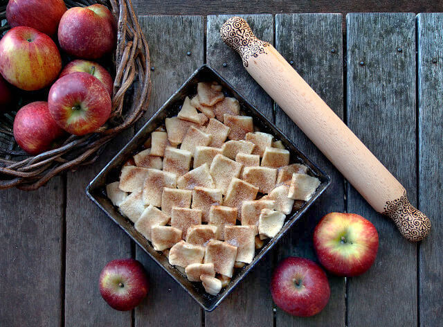 Overhead view of a square pan of apple pandowdy with unbaked pastry crust, surrounded by apples and a wooden rolling pin.