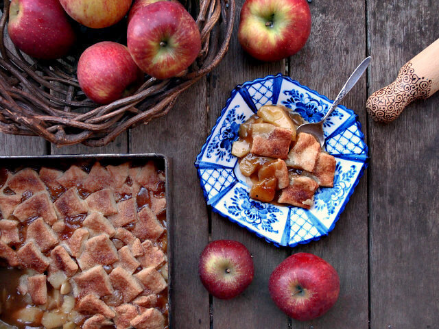 Overhead view of a plate of apple pandowdy surrounded by apples and a wooden rolling pin.