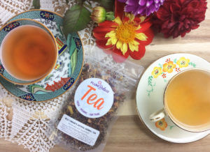 Overhead view of a bag of loose leaf herbal tea surrounded by two teacups and flowers.