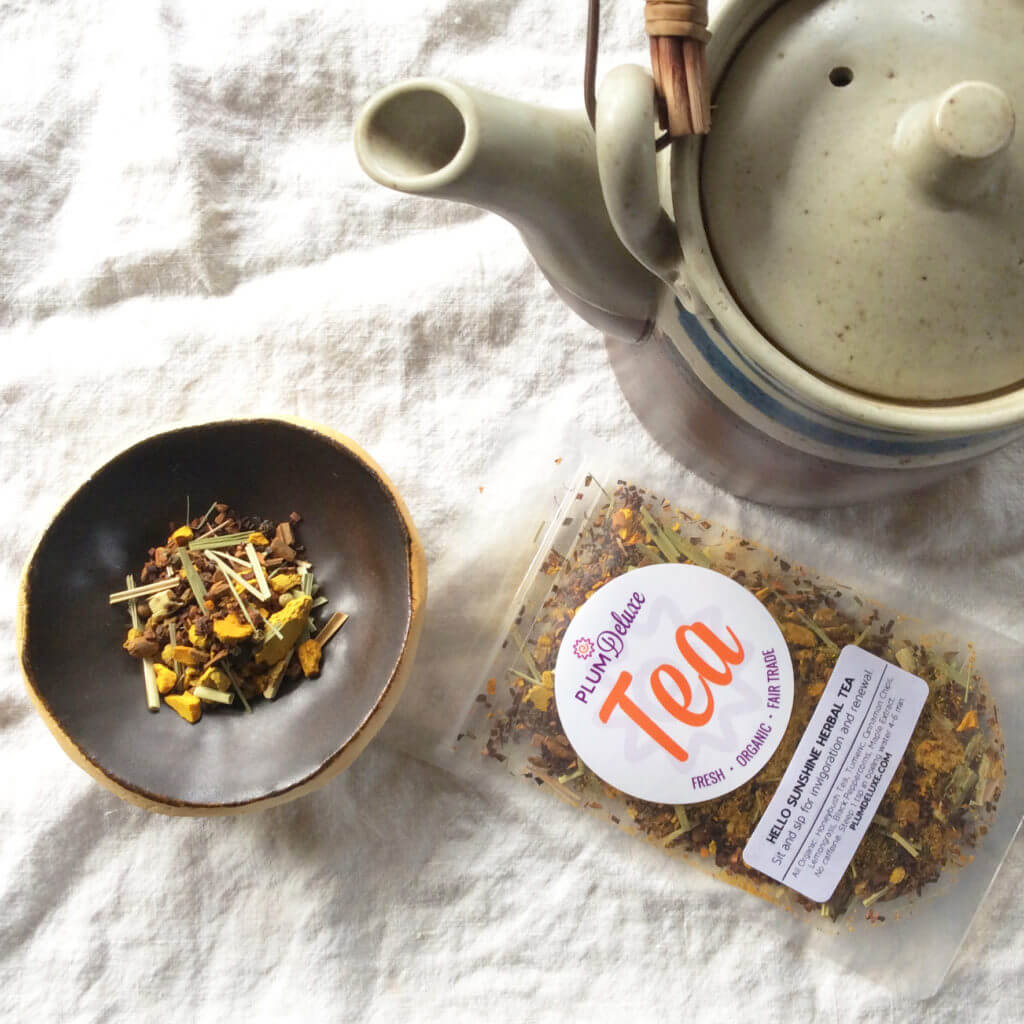 Overhead view of a bag of turmeric loose leaf herbal tea next to a clay teapot.
