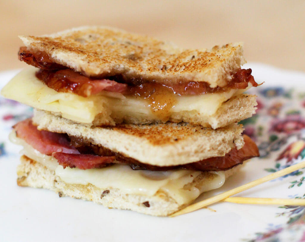 Two apple butter ham and cheese tea sandwiches are stacked on a white plate with floral border.