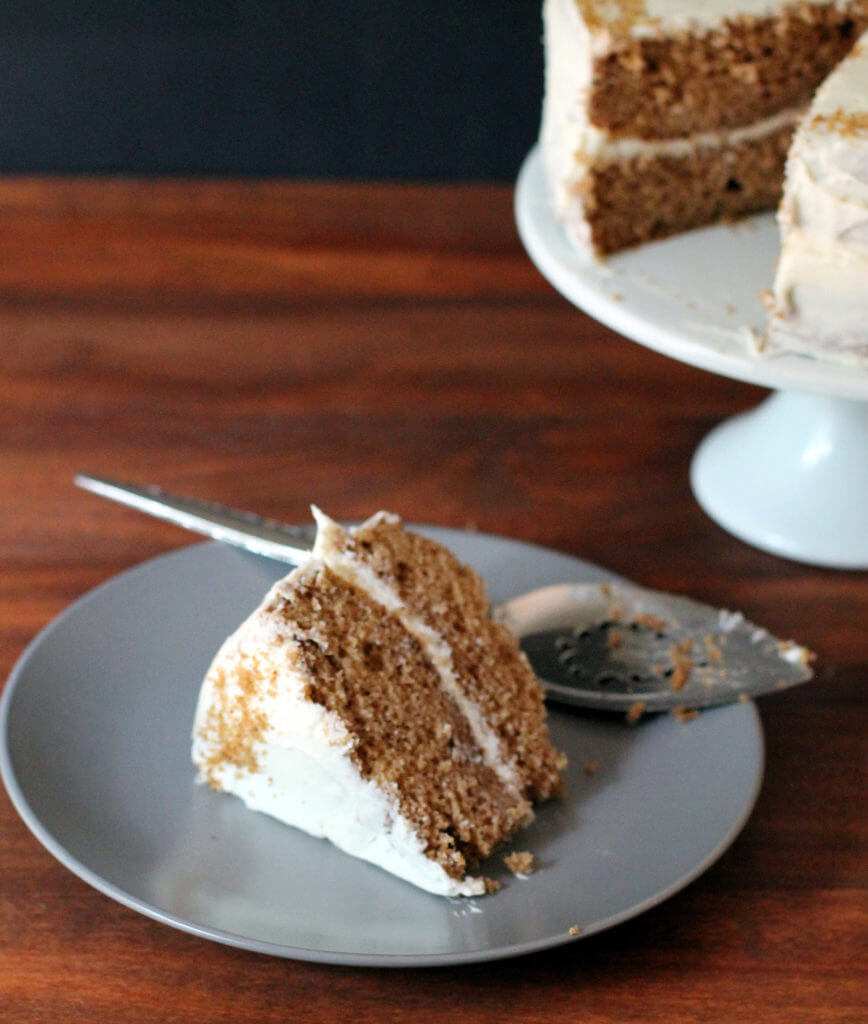 A slice of homemade spice cake sits on a plate with a cake on a cake stand in the background.