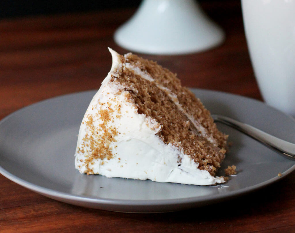 A slice of homemade spice cake sits on its side on a plate.