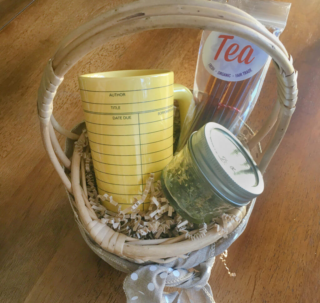 A wooden gift basket holds a mason jar of loose leaf tea, a yellow mug, and a package of honey sticks.
