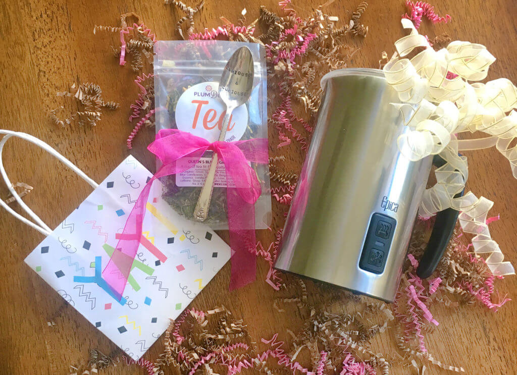 """Overhead view of an electric milk frothing pitcher, a teaspoon tied to a bag of loose leaf tea with a bright pink ribbon, and a gift bag that says """"YAY!"""""""