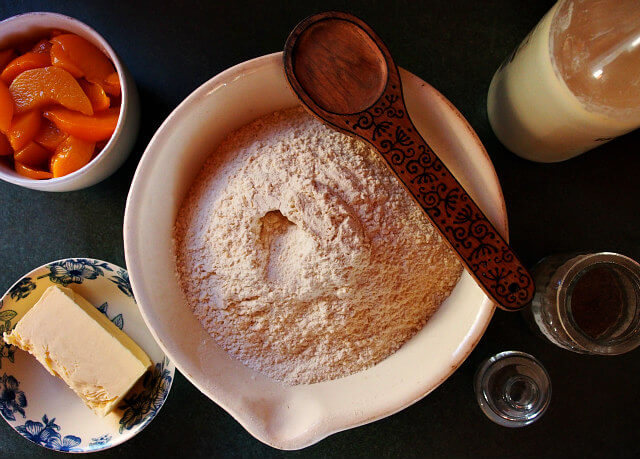 Overhead view of ingredients for peach cardamom scones, including flour, peaches, and butter.