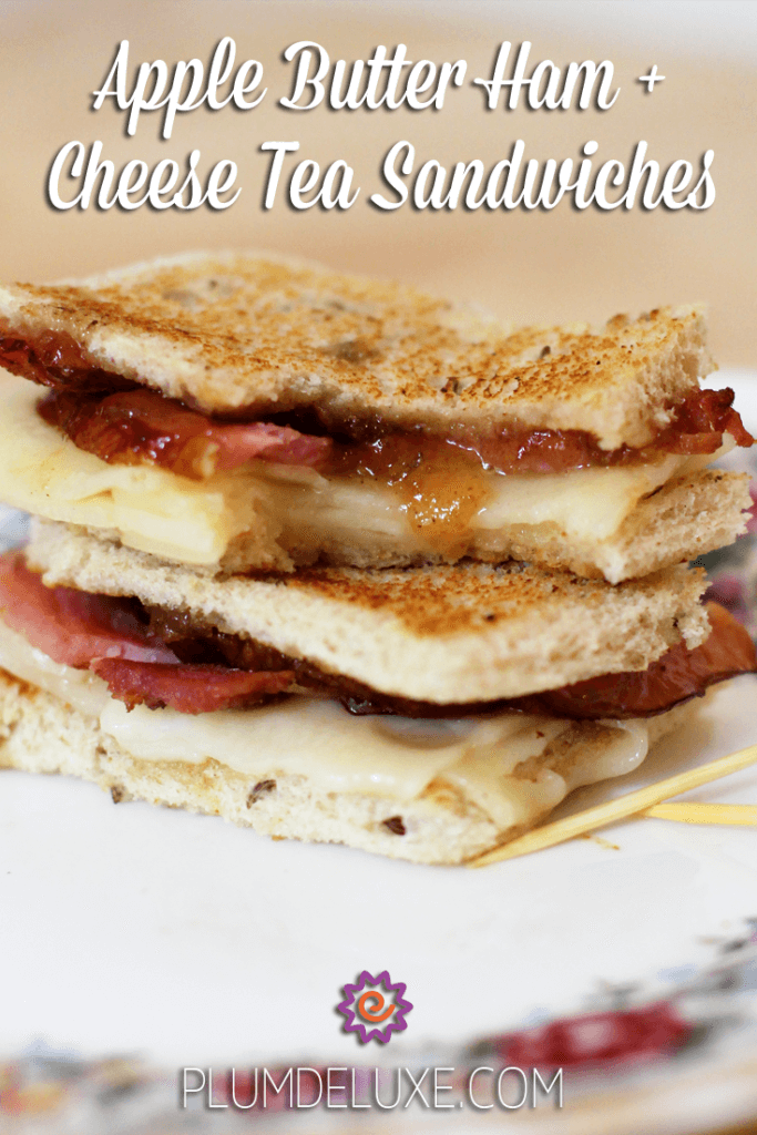 Two apple butter ham and cheese tea sandwiches are stacked together on a white plate.
