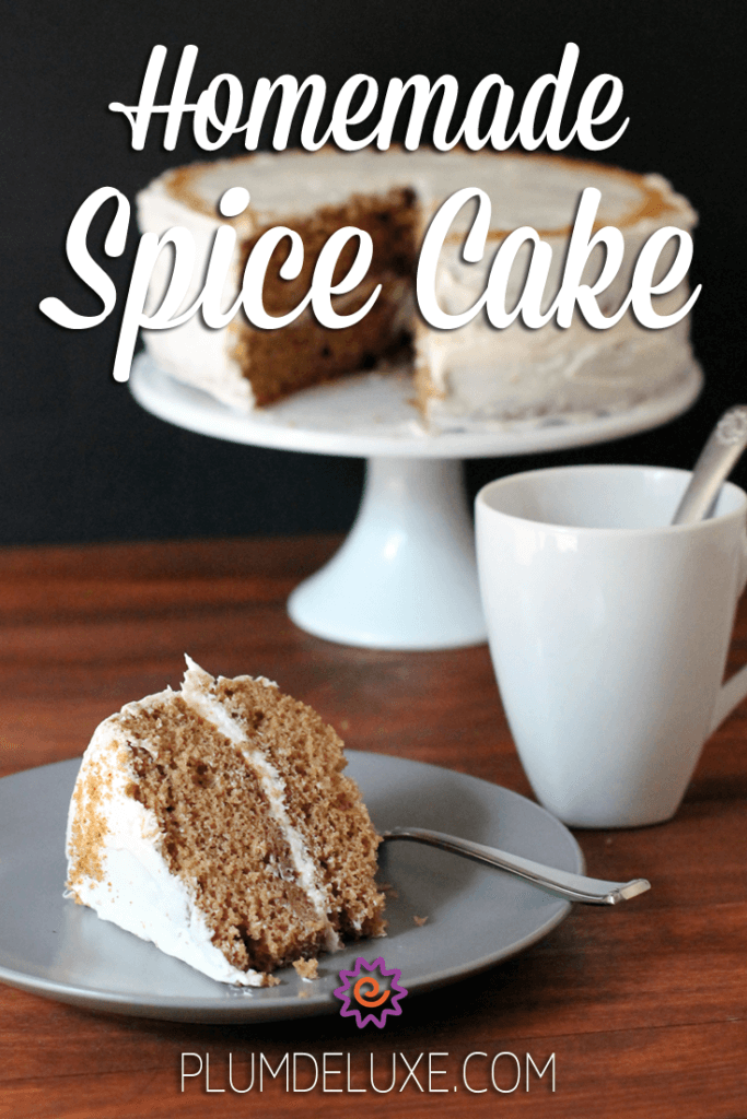A slice of homemade spice cake sits on a plate with a mug of tea and a cake on a cake stand in the background.