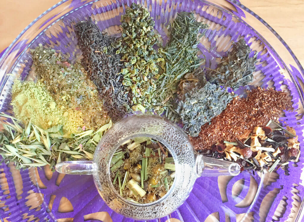 Overhead view of various kinds of loose leaf teas surrounding a clear glass teapot.
