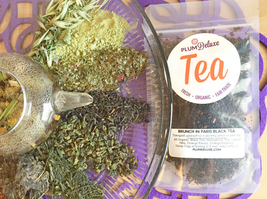Overhead view of various kinds of loose leaf teas surrounding a clear glass teapot. A bag of loose leaf black tea sits to the side.