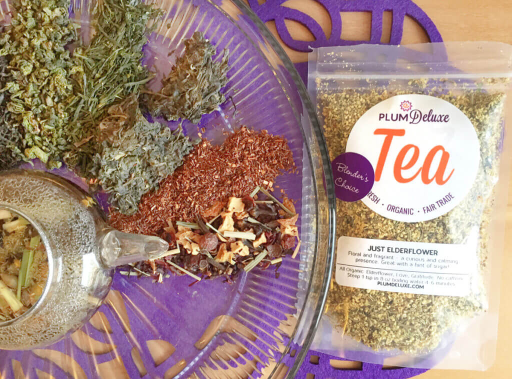 Overhead view of various kinds of loose leaf teas surrounding a clear glass teapot. A bag of loose leaf herbal tea sits to the side.