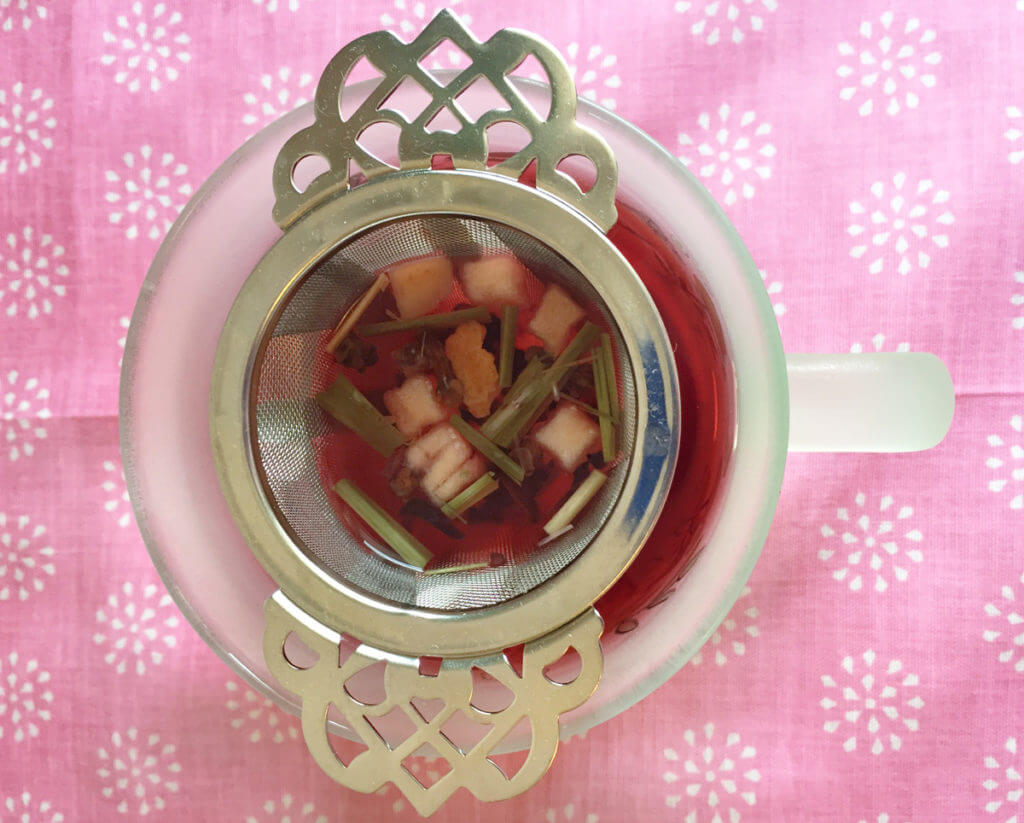Overhead view of a mug with loose leaf tea in a victorian style tea infuser.