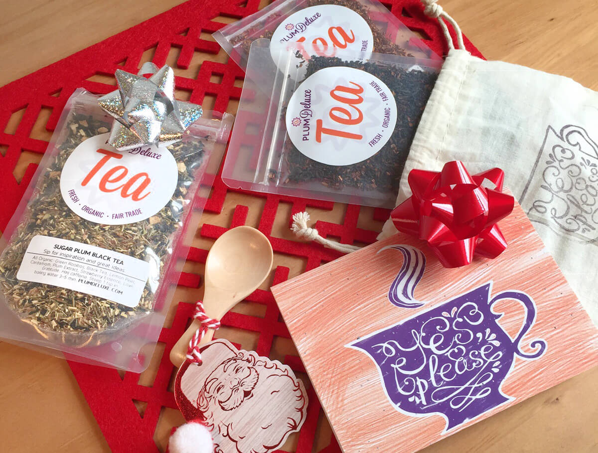 "A trio of Plum Deluxe loose leaf teas, a gift bag that says ""Yes, Please,"" a wooden tea scoop, and a card are scattered on a red mat."